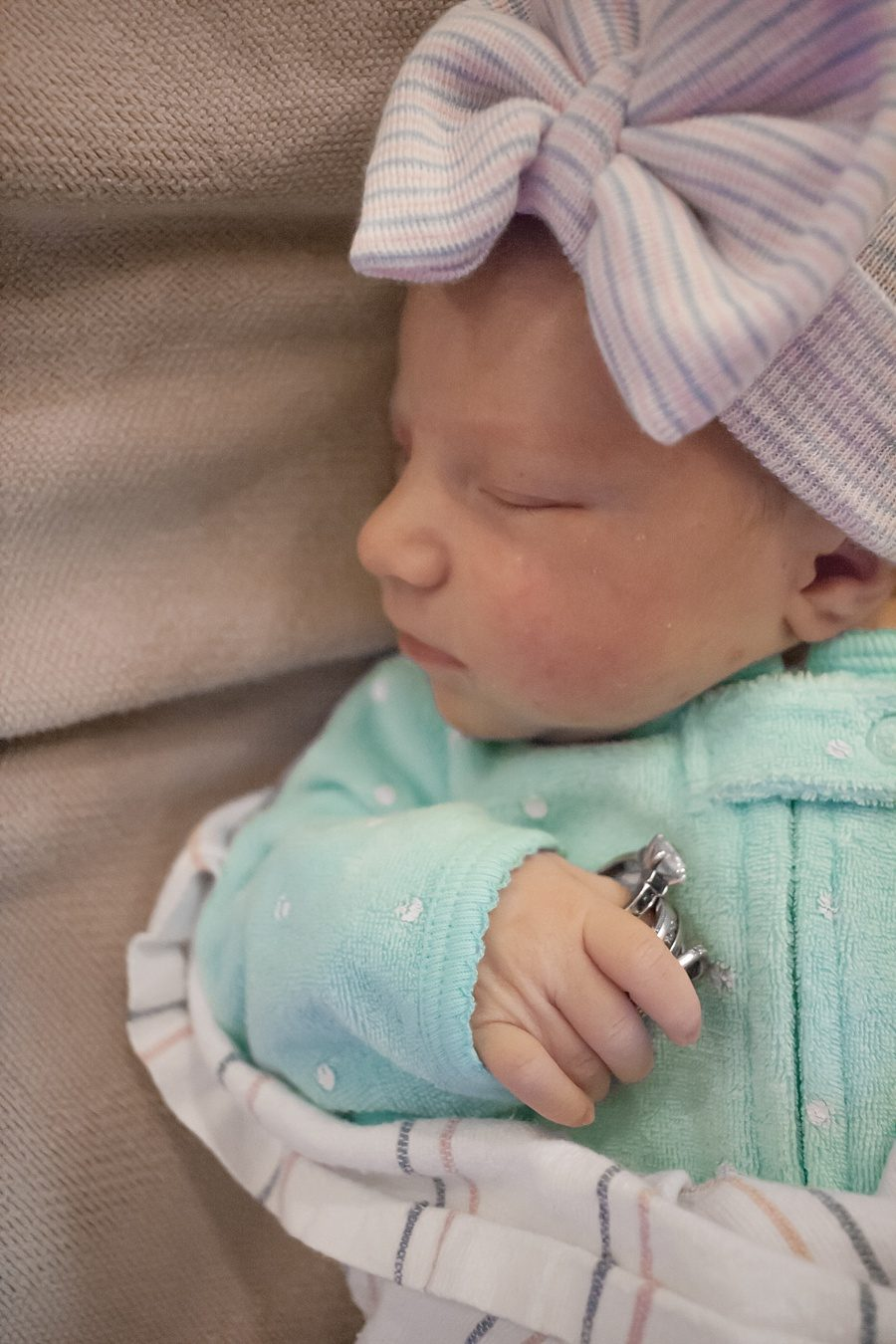 close up of newborn baby girl with wedding rings fresh 48 hospital photography