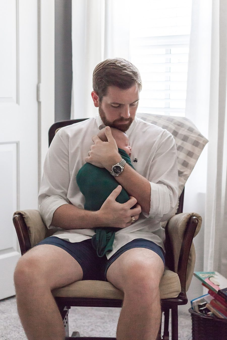 dad holding newborn in casual family newborn session in the woodlands texas