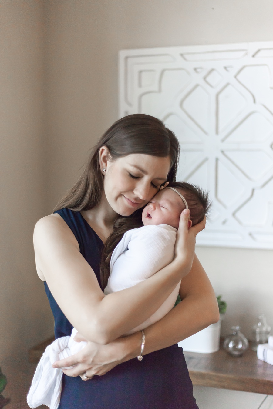 new mom holding newborn for in-home newborn photography session