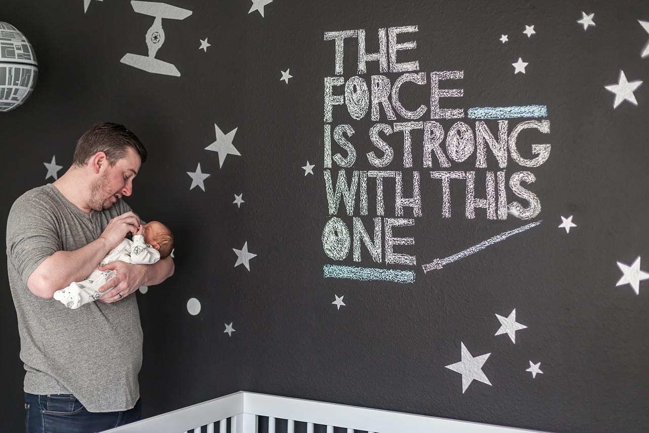dad holds baby boy in star wars nursery