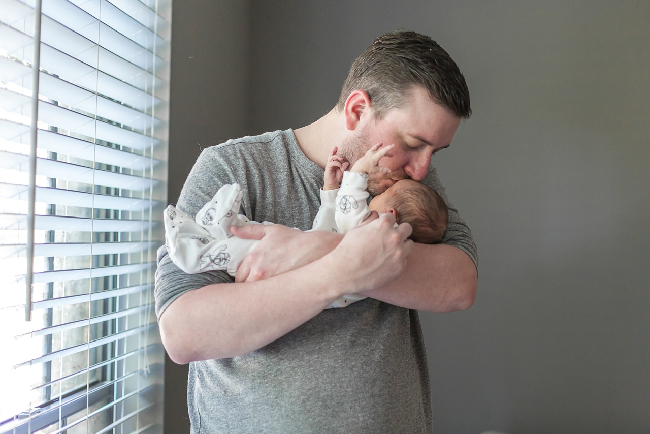 new father kissing newborn son in the woodlands, texas