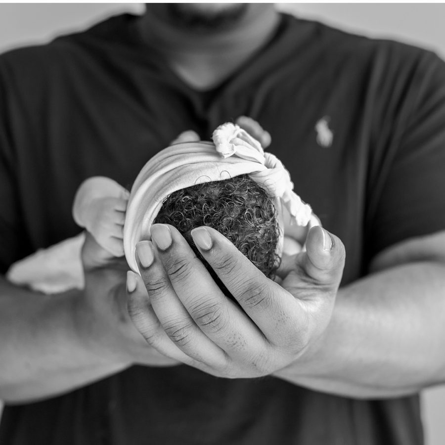 newborn baby girl in dad's hands during at-home newborn photos by kristal bean photography