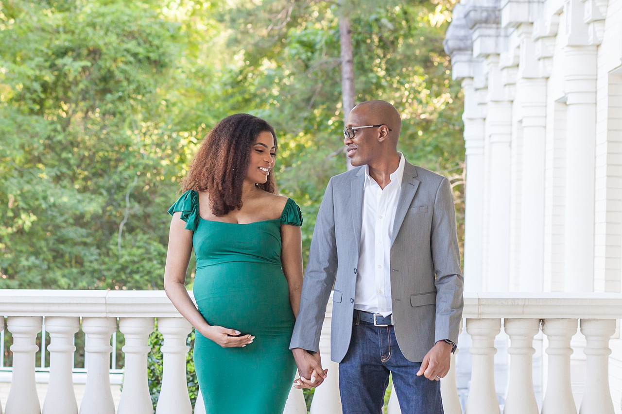 radiant mom-to-be in green stands with her husband in the woodlands texas during a maternity photo session by kristal bean photography