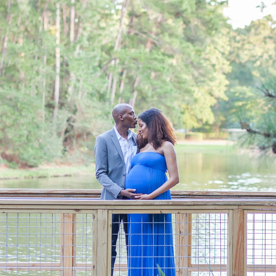 beautiful couple pictured on a bridge during a sunset maternity session in the woodlands texas by kristal bean photography