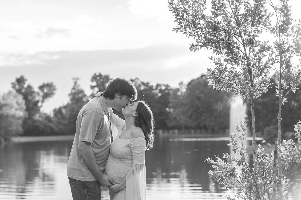 creekside park maternity photography session at sunset featuring pregnant mom in flowing gown