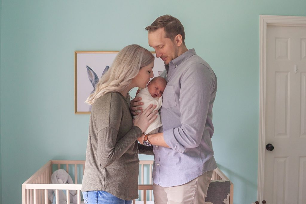 mom kisses newborn baby with dad looking on during newborn session with kristal bean photography
