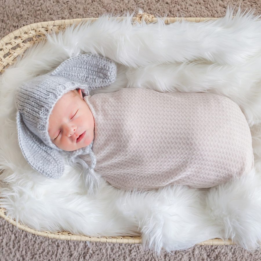 in-home newborn photo featuring baby boy in rabbit hat by kristal bean photography