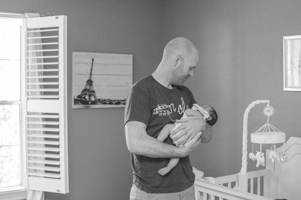 new dad holds baby girl during newborn photo session by kristal bean photography