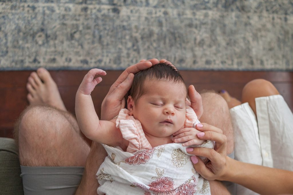 newborn baby girl sleeps with parents during in-home newborn session by kristal bean photography
