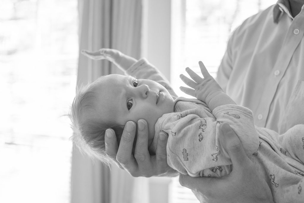 newborn baby boy looks at camera during at-home newborn photo session in the woodlands texas