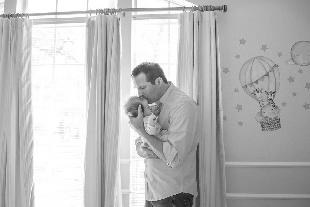 new father kisses newborn son in baby blue nursery in the woodlands texas