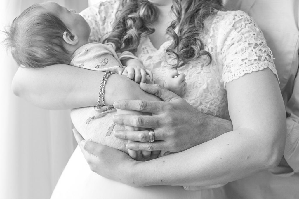 mom and dad hold newborn with focus on family's hands by kristal bean photography