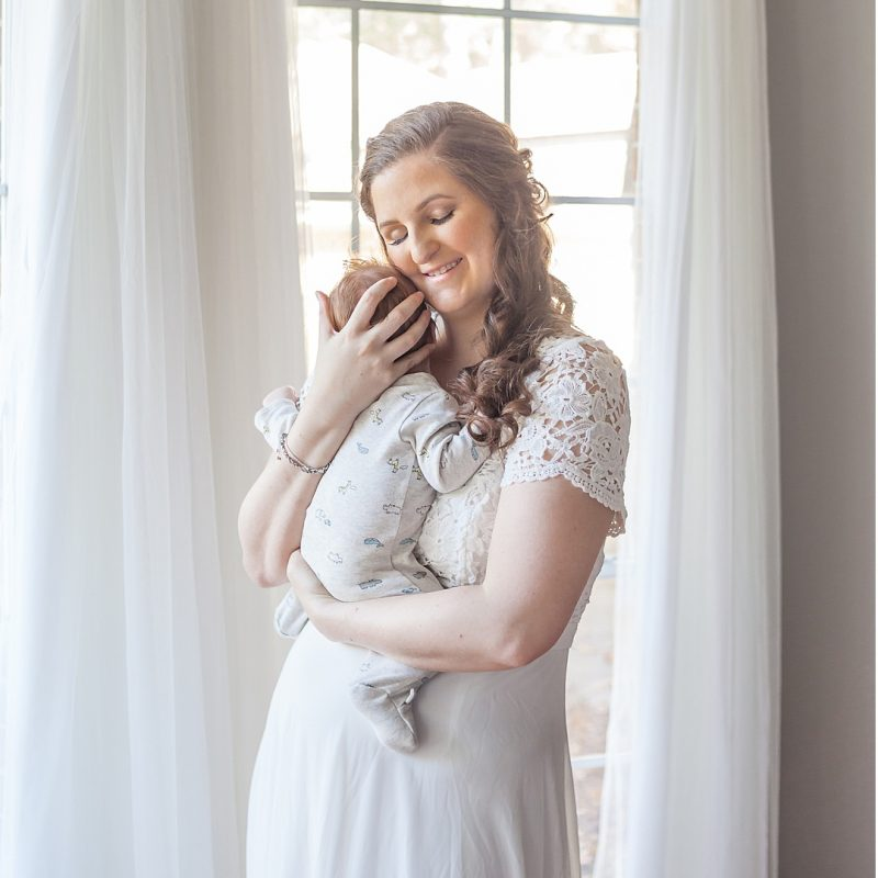 new mom snuggles with newborn baby boy in the woodlands texas photo session by kristal bean