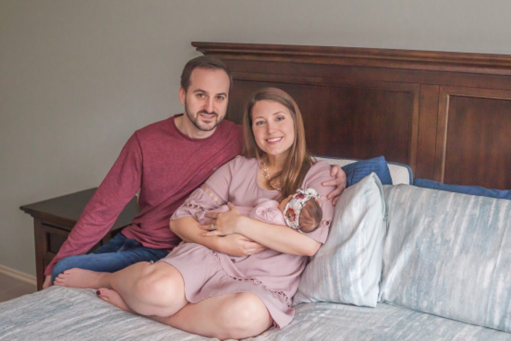 new parents hold two-week-old daughter in at-home newborn photography by kristal bean photography