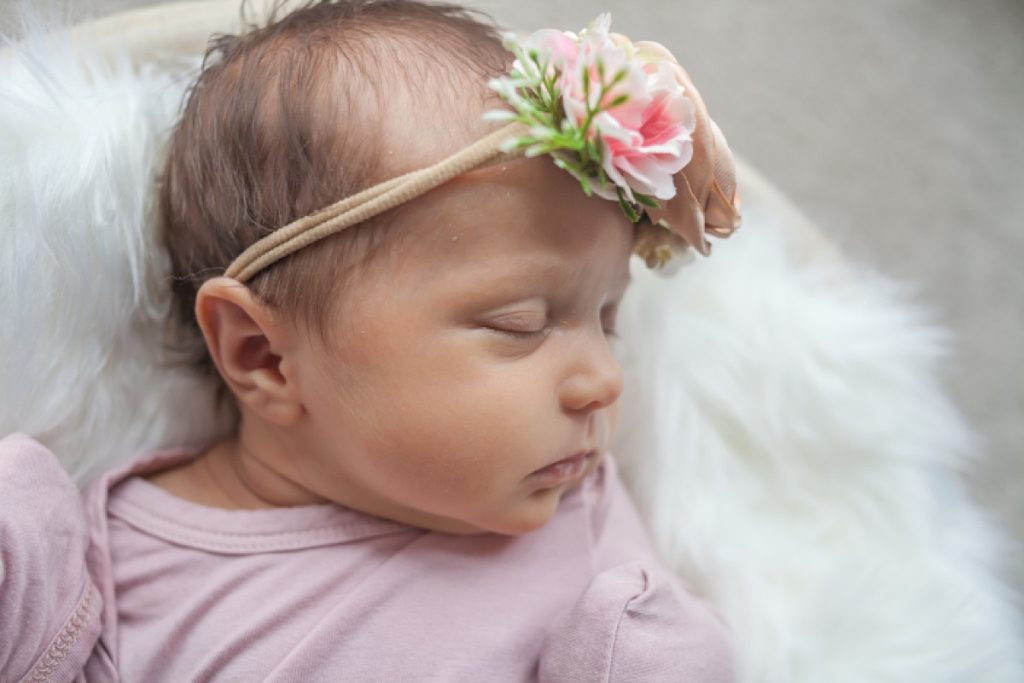 closeup of two-week-old newborn in tiny flower crown by kristal bean photography