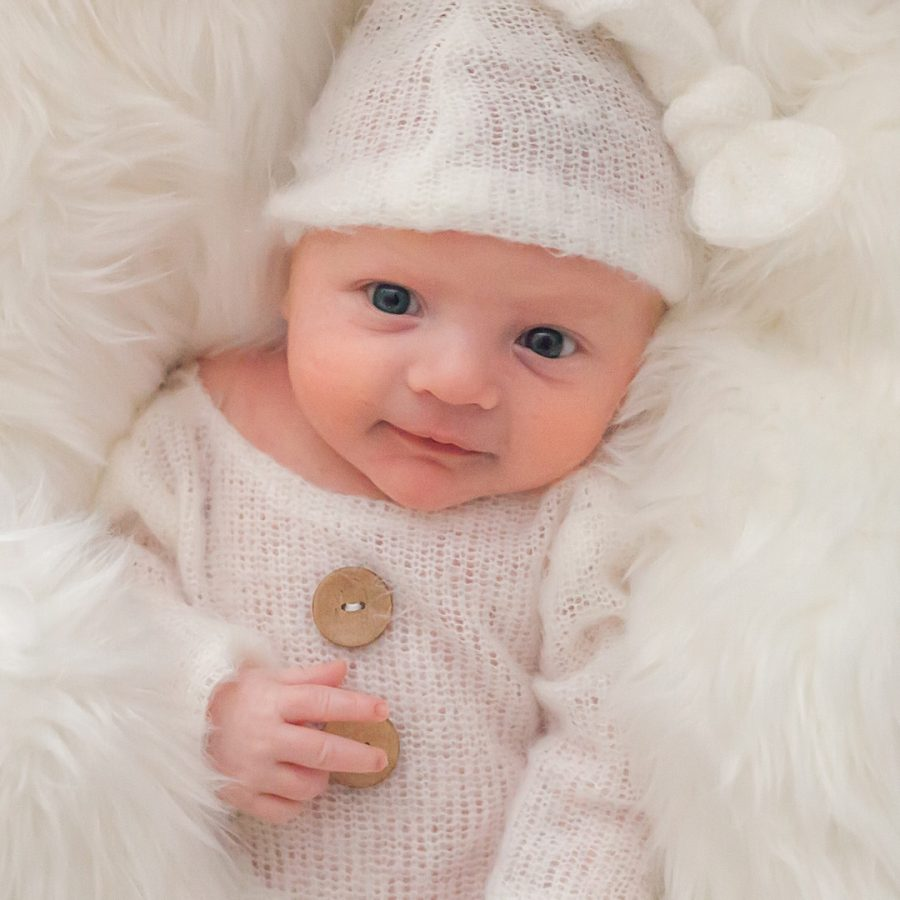 newborn boy in white during at-home newborn session